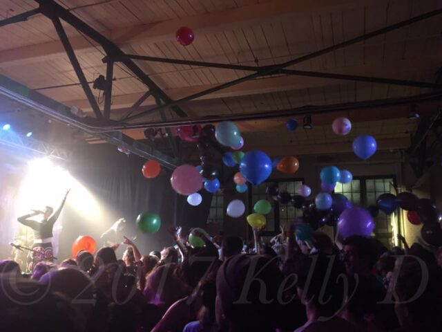 Kal Traver gesticulates amongst balloons at Gateway City Arts in Holyoke, MA - 12.30.17
